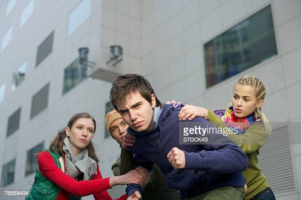 Group keeping back young aggressive man