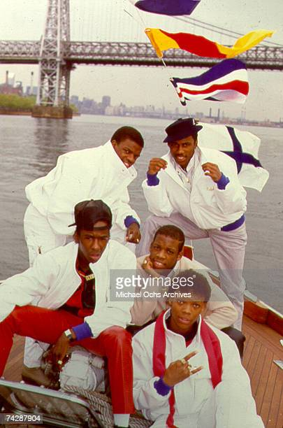 B group New Edition pose for a portrait on a boat in the East River with the Williamsburg Bridge in the background in 1985 in New York City New York