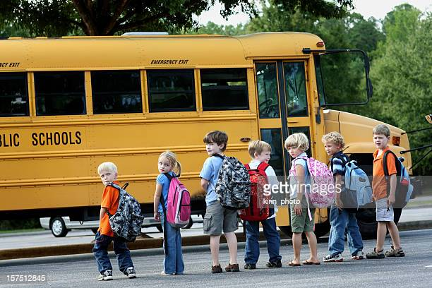 Group od first graders in front of school bus.