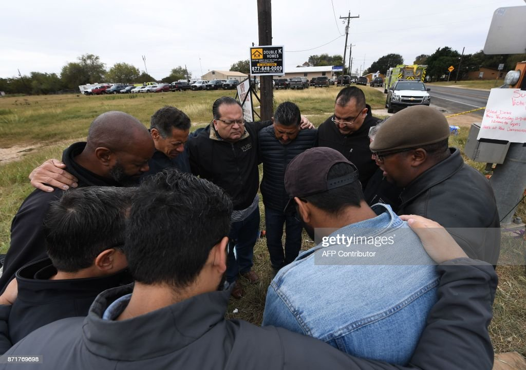 A group of 12 pastors from local churches, pray beside a memorial service for victims of the mass shooting that killed 26 people in Sutherland Springs, Texas on November 8, 2017. A gunman wearing all black armed with an assault rifle opened fire on a small-town Texas church during Sunday morning services, killing 26 people and wounding 20 more in the last mass shooting to shock the United States. /