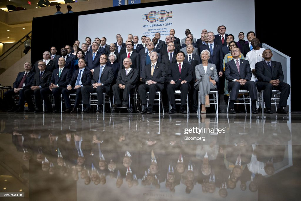Group of 20 (G-20) finance ministers and central bank governors including Ignazio Visco, governor of the Bank of Italy, front row left, Pier Carlo Padoan, Italy's finance minister, Nicolas Dujovne, Argentina's treasury minister, Jens Weidmann, president of the Deutsche Bundesbank, Wolfgang Schaeuble, Germany's finance minister, Zhou Xiaochuan, governor of the People's Bank of China, Zhu Guangyao, China's vice minister of finance, Christine Lagarde, managing director of the International Monetary Fund (IMF), and Jim Yong Kim, president of the World Bank Group, sit for a group photo on the sidelines of the IMF and World Bank Group Annual Meetings in Washington, D.C., U.S., on Thursday, Oct. 12, 2017. Near-term risks to world financial stability have declined since April amid improving macroeconomic conditions and the subsiding risk of emerging-market turmoil, the IMF said in its latest Global Financial Stability Report released yesterday. Photographer: Andrew Harrer/Bloomberg via Getty Images