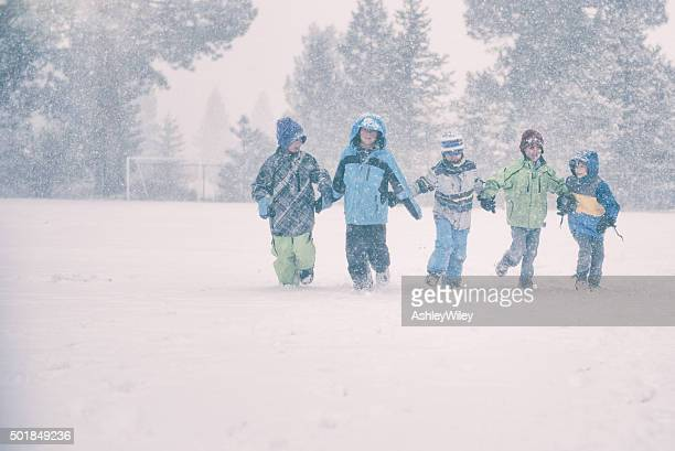 Group of 5 children run in a snowy storm