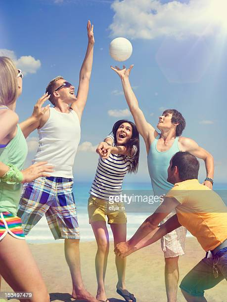 Group of 5 friends having fun with volleyball on the beach
