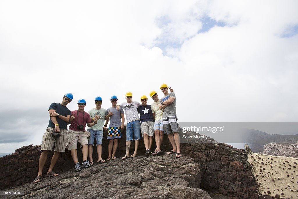 A group of 8 middle aged men in front of a volcano : Stock Photo