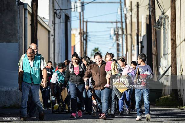 A group of about 30 undocumented immigrants makes their way through an alley to Sacred Heart Catholic Church Charities in McAllen Tx where they will...