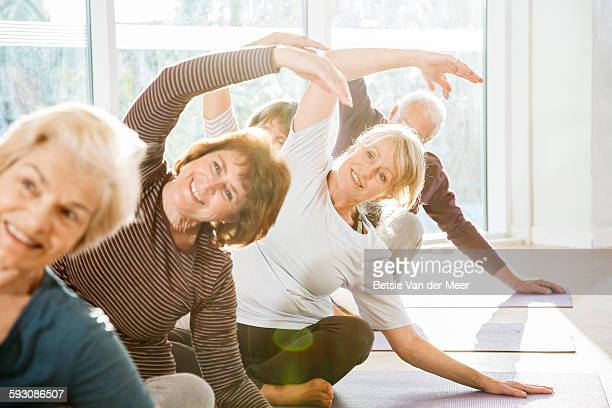 Group of active seniors exercise in yoga class.