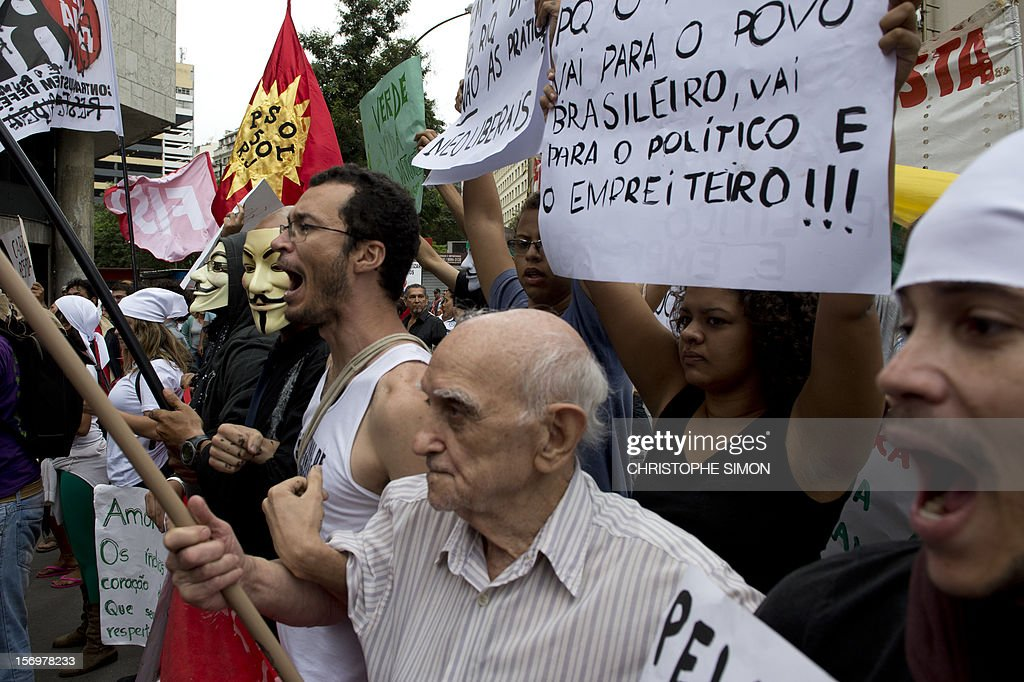 A group of activists shout slogans against thousands of demonstrators demanding Brazilian President Dilma Roussef to veto a bill that would redistribute oil royalties in favor of non-oil producing states, in Rio de Janeiro, Brazil, on November 26, 2012. Both Rio de Janeiro's mayor Eduardo Paes and governor Sergio Cabral warned that the new oil royalties share-out plan will jeopardize the financing of the 2014 World Cup and the 2016 summer Olympics. AFP PHOTO/Christophe Simon