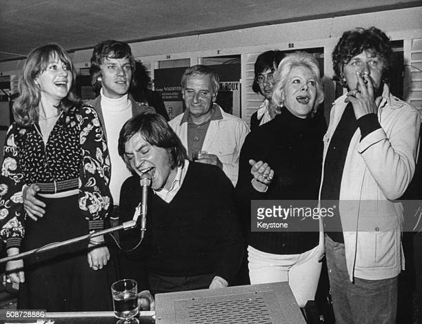 A group of actors singing around a piano while attending the Cannes Film Festival Helen Mirren Malcolm McDowell Alan Price Lindsay Anderson Rachel...