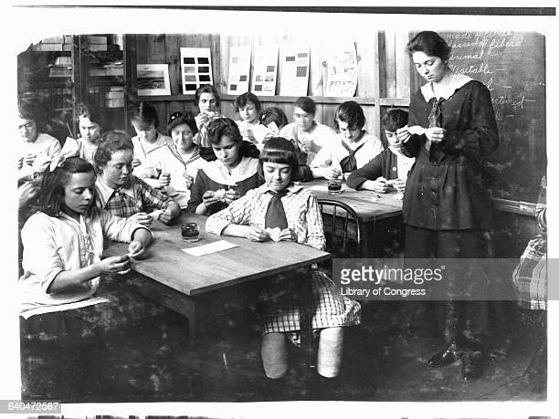 A group of adolescent girls learn about different textiles at Ipswich Mills in South Boston | Location Ipswich Mills South Boston Massachusetts USA