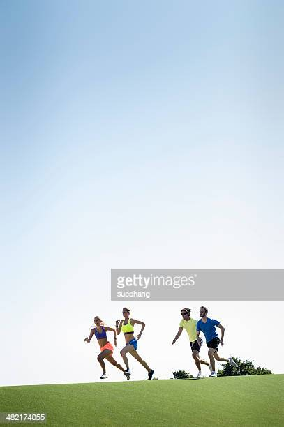 Group of adult runners running in park