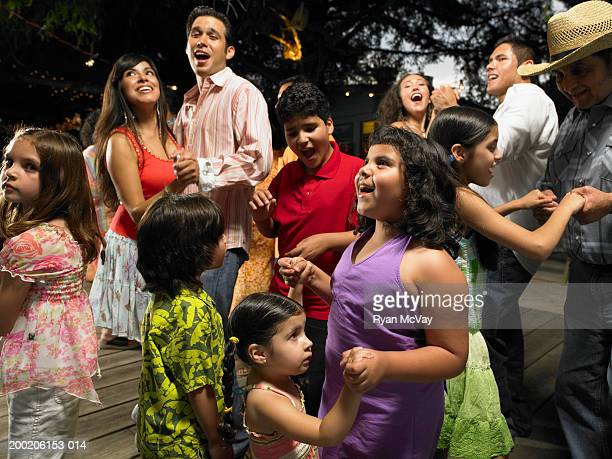 Group of adults and children (3-11) dancing and singing