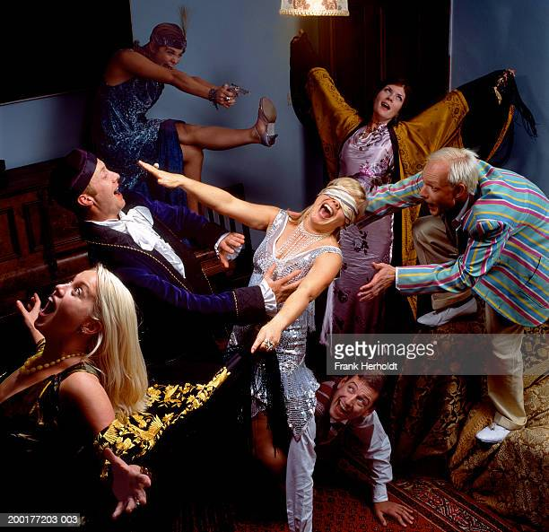Group of adults at fancy dress party in living room