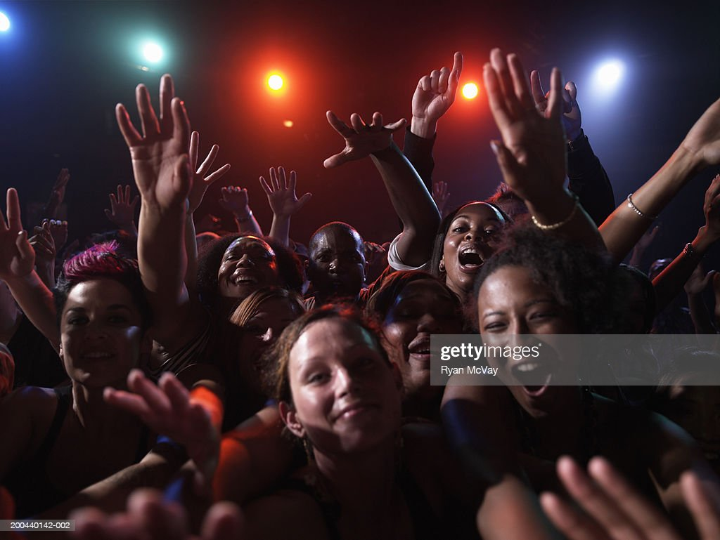 Group of adults cheering in nightclub, arms raised, portrait : Stock Photo