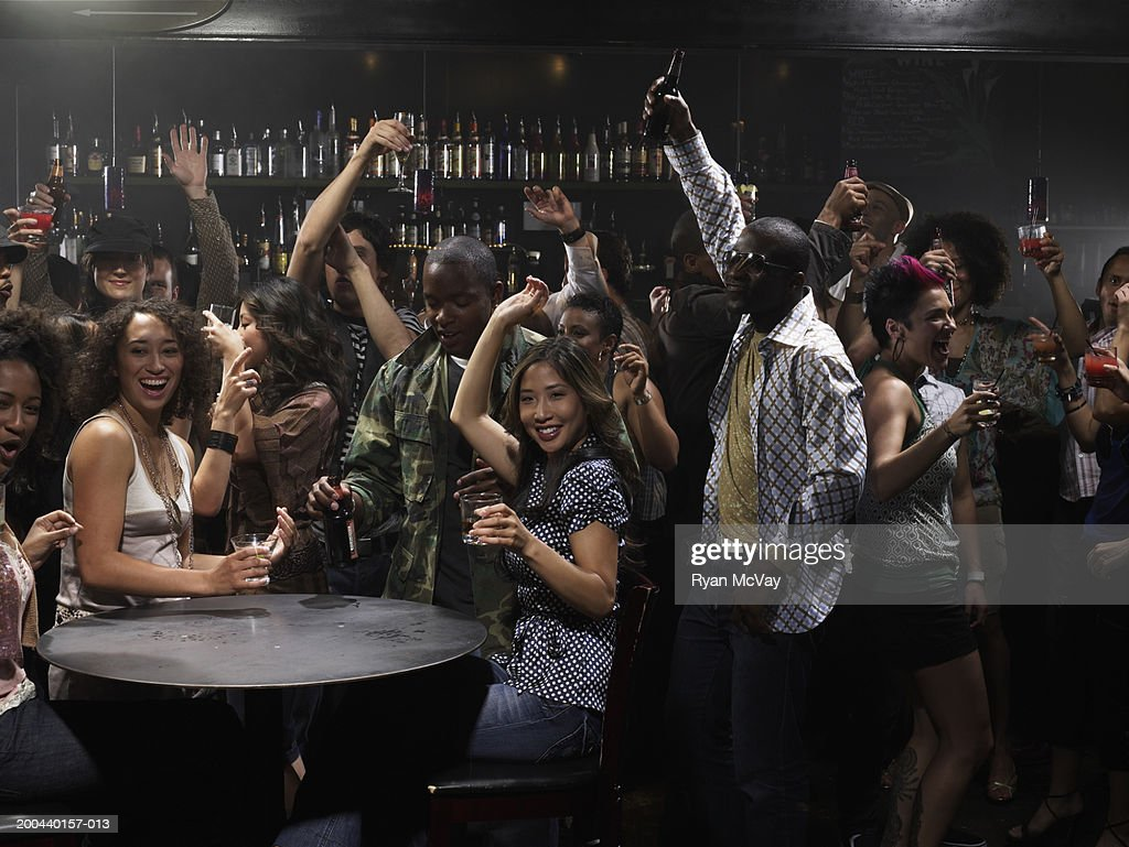Group of adults drinking cocktails and cheering in club, arms raised : Stock Photo