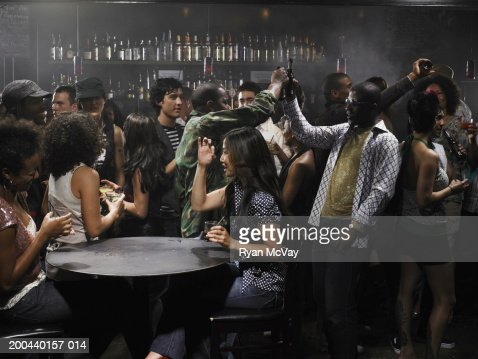 Group of adults drinking cocktails and talking in nightclub : Stock Photo