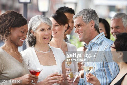 Group of adults drinking wine and cocktails, smiling