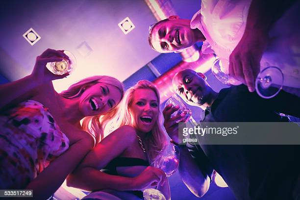 Group of adults having fun in club on weekend night.