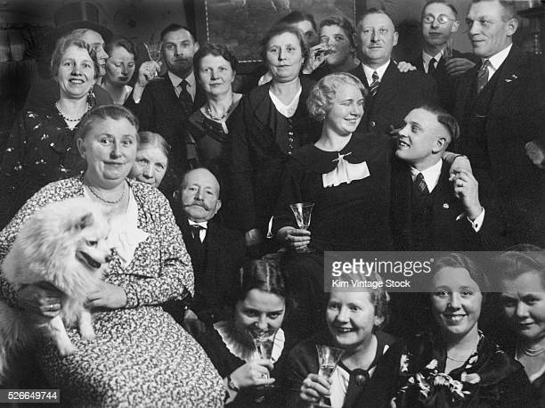 A group of adults pose with their drinks and one dog for a party portrait in preWorld War II Germany