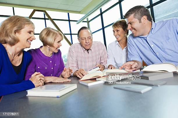 Group of adults reading in a library together
