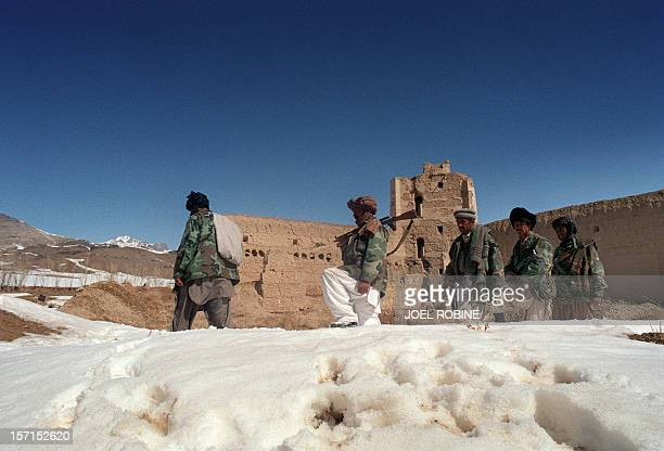 A group of Afghan mujahedeen progress in the snow 05 March 1989 behind a wall in a village of Ghazni province in southern Afghanistan to reach...