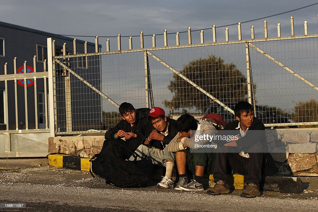 A group of Afghan youths rest on a roadside as they walk to the town of Mytilene hours after arriving by boat from Turkey in the northern part of the island of Lesbos, Greece, on Saturday, Dec. 8, 2012. In recent months, Lesbos has become a hot spot for migrants as Greece struggles to cope with waves of refugees from Middle Eastern conflict even as it reels from economic crisis at home. Photographer: Kostas Tsironis/Bloomberg via Getty Images