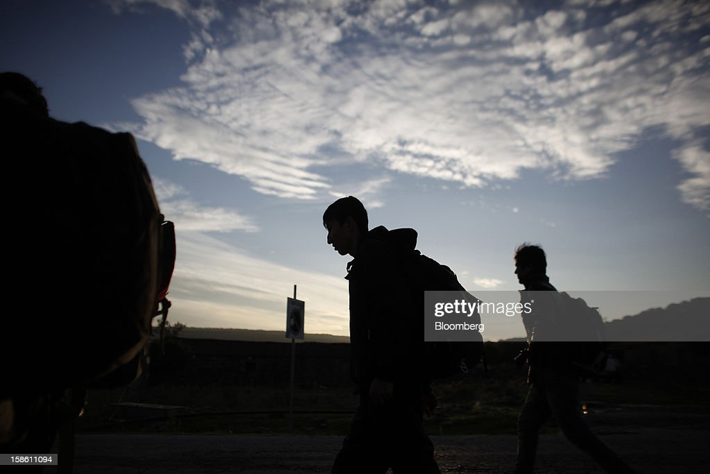A group of Afghan youths walk along a road in Mantamados towards the town of Mytilene after arriving by boat from Turkey in the northern part of the island of Lesbos, Greece, on Saturday, Dec. 8, 2012. In recent months, Lesbos has become a hot spot for migrants as Greece struggles to cope with waves of refugees from Middle Eastern conflict even as it reels from economic crisis at home. Photographer: Kostas Tsironis/Bloomberg via Getty Images