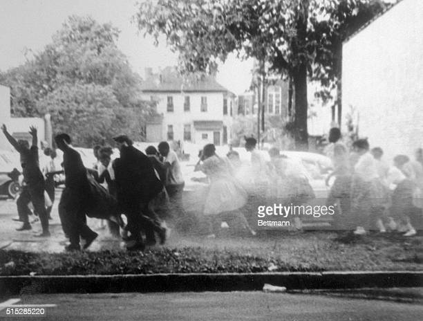 A group of African American antisegregation demonstrators run for safety as they are sprayed with highpressure water from fire hoses during a civil...