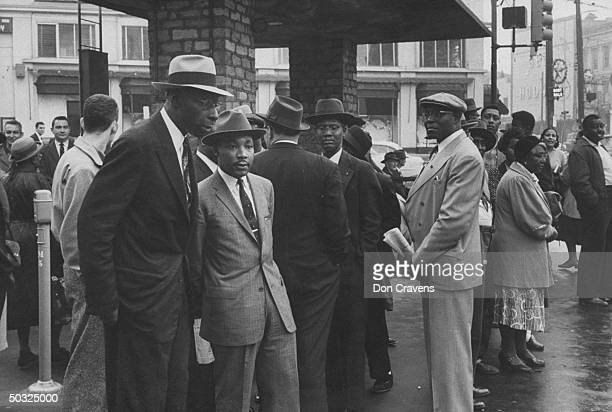 Group of African Americans including Rev Martin Luther King waiting at busy bus stop following Supreme Court ruling ending successful 381 day boycott...