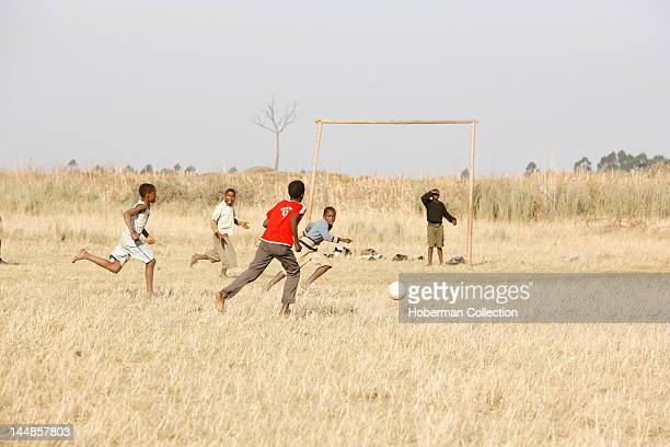 Group of African Children playing soccer / football in the Townships Cape Town South Africa