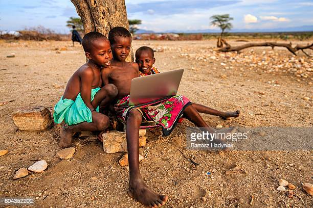 Group of African children using laptop, Kenya, East Africa