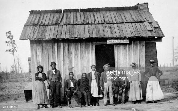 A group of AfricanAmericans pose outside a clapboard storefront late 1800s or early 1900s A sign that hangs over the doorway advertises CocaCola for...