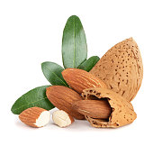 Group of almond nuts with leaves isolated on a white background.