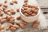 group of almonds  from wood bowl on wood background