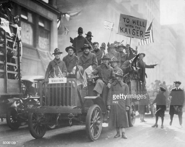 A group of American soldiers ride in a truck waving American flags during an Armistice Day parade celebrating the end of World War I New York City...