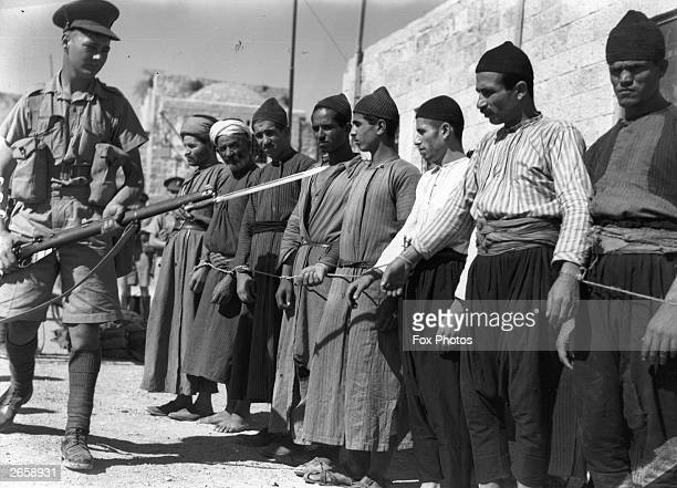 A group of Arab prisoners in the Old City of Jerusalem is guarded by a soldier armed with a rifle and bayonet