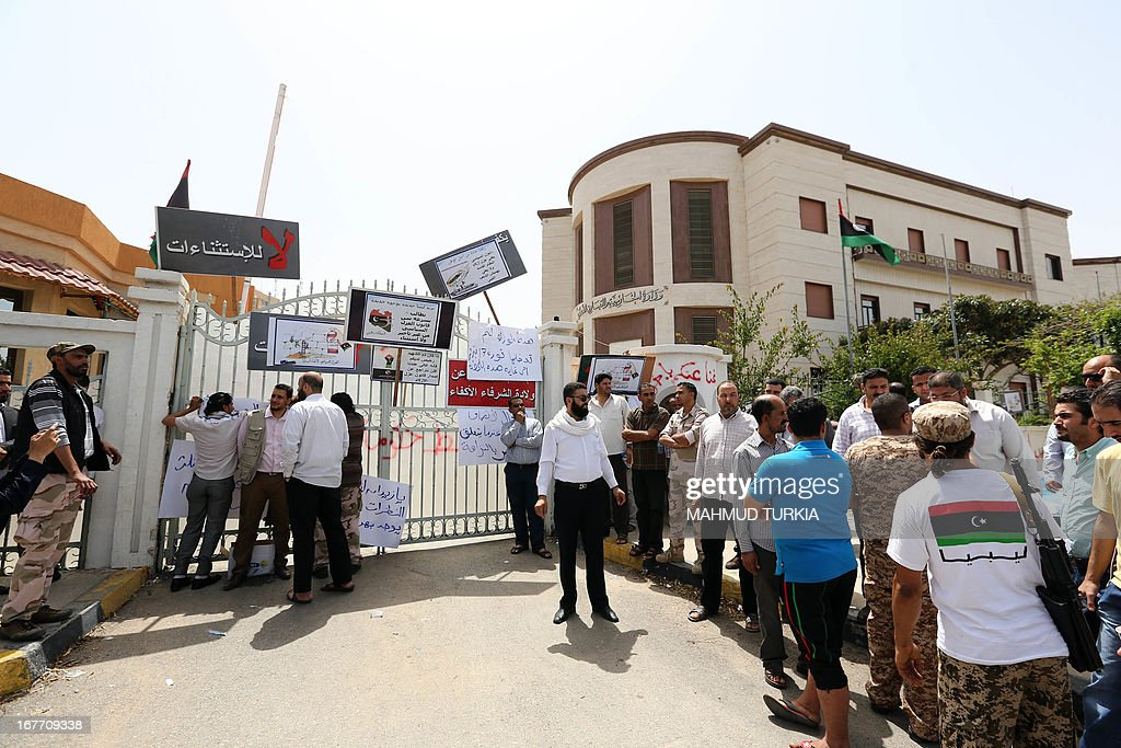 A group of armed block the entrance of the foreign ministry as they demand it be 'cleansed of agents' and ambassadors of ousted dictator Moamer Kadhafi on April 28, 2013 in the Libyan capital Tripoli. The group prevented staff from entering the building said a ministry official who spoke to AFP. The General National Congress, Libya's highest political authority, is studying proposals for a law to exclude former Kadhafi regime officials from top government and political posts.