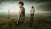 Group of asian scary zombies standing on dry grass field with dramatic sky background