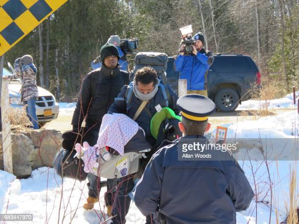 A group of asylum seekers two men a woman and a baby cross the border illegally from the United States into Canada near SaintBernarddeLacolle Que on...