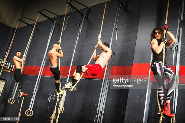 group of athlete climbing the rope on a gym
