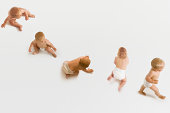 Row of babies sitting; crawling and walking on white background