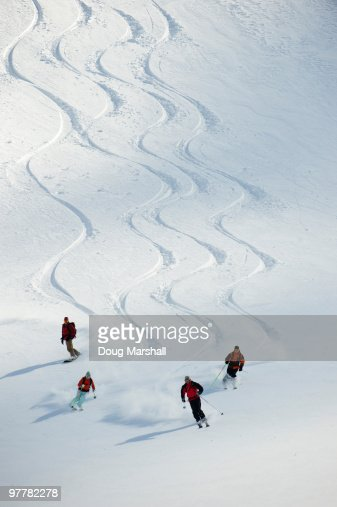 A group of backcountry skiers follow their guide down a slope in the Selkirk Mountains, Canada.