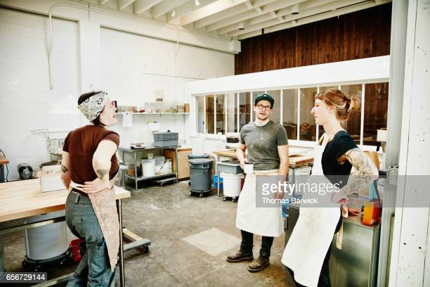 Group of bakers in discussion while taking a break during morning production