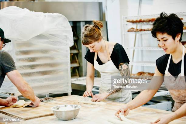 Group of bakers shaping dough for bread in bakery