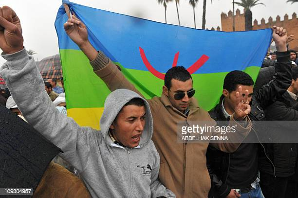 A group of Berber people hold their flag as they gather for a protest in Morocco on February 20 2011 in Rabat Several thousand people rallied in...