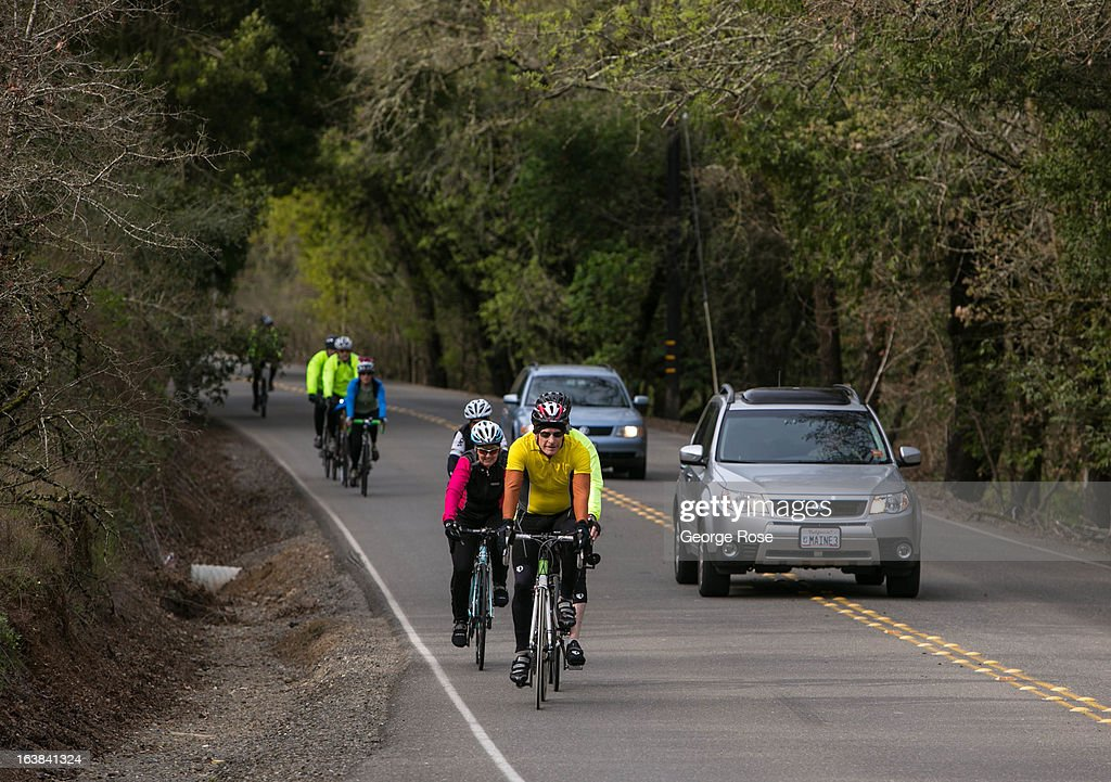 A group of bicyclists wind their way along a narrow rural backroad on March 15, 2013, near Santa Rosa, California. Sonoma County, along with Napa Valley, has grown to become one of California's most prestigious wine grape growing regions and known for its cool climate pinot noir and chardonnay.