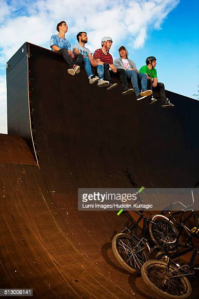 Group of BMX bikers taking a break on a sports ramp