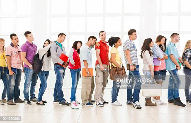 Group of bored students standing in a line and waiting.