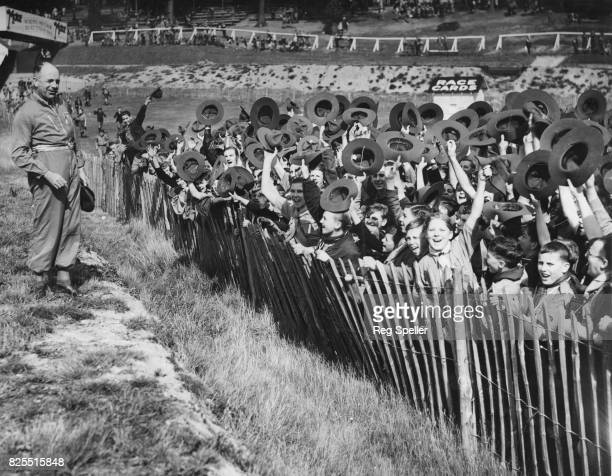 A group of Boy Scouts cheer racing driver Francis Curzon 5th Earl Howe at Brooklands race track UK after he invited them for a day out at the track...