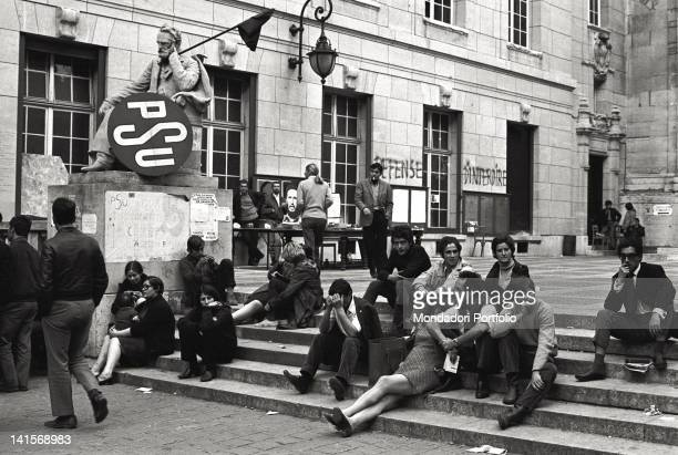 A group of boys and girls are sat down on the stairs at the entrance of the Sorbonne headquarter next to the statue of Victor Hugo On the statue a...