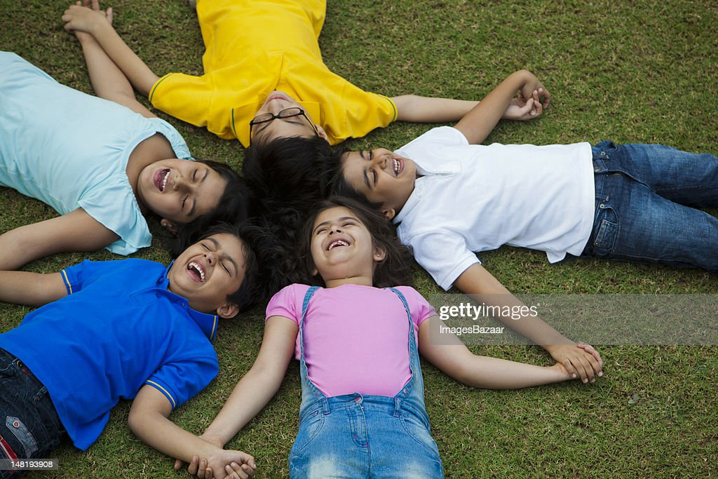 Group of boys and girls (6-7, 8-9) lying on grass in circle : Stock Photo